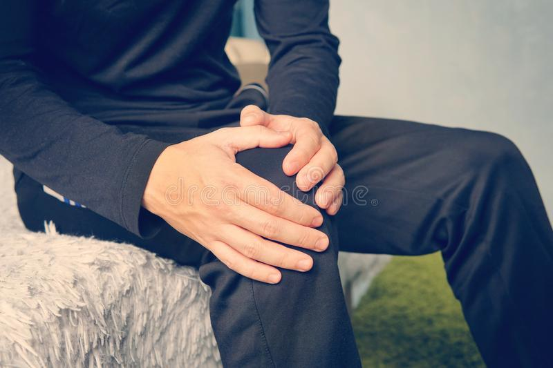Young man suffering from leg pain at home stock images