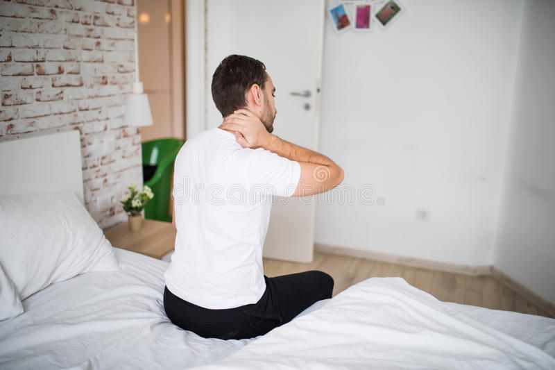 Young man suffering from neck ache in bed at home. Man suffering from neck ache in bed at home royalty free stock photos