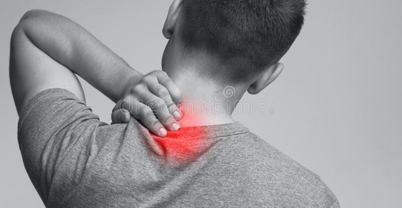 Young man suffering from neck ache, monochrome panorama photo. Body pain. Young man suffering from neck ache, monochrome panorama photo with red inflamed zone royalty free stock image