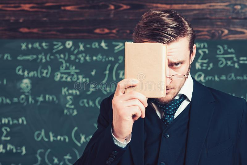 Young man in suit covering his face with book. Closeup portrait of young blond aristocrat with stylish hair and beard royalty free stock photos