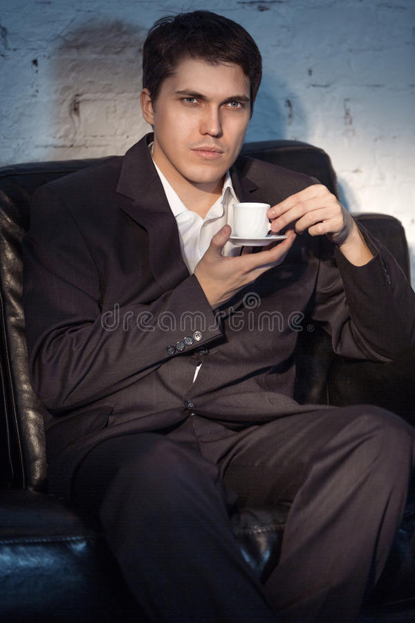 Young man in suit drink coffee. Young man in suit sitting on sofa and drink coffee stock image