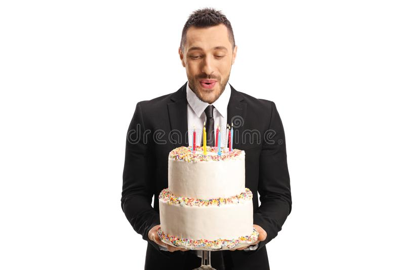 Young man in a suit holding a birthday cake and blowing candles stock images