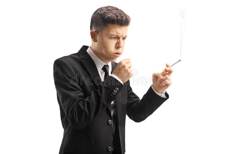 Young man in a suit holding a cigarette and coughing. Isolated on white background stock photos