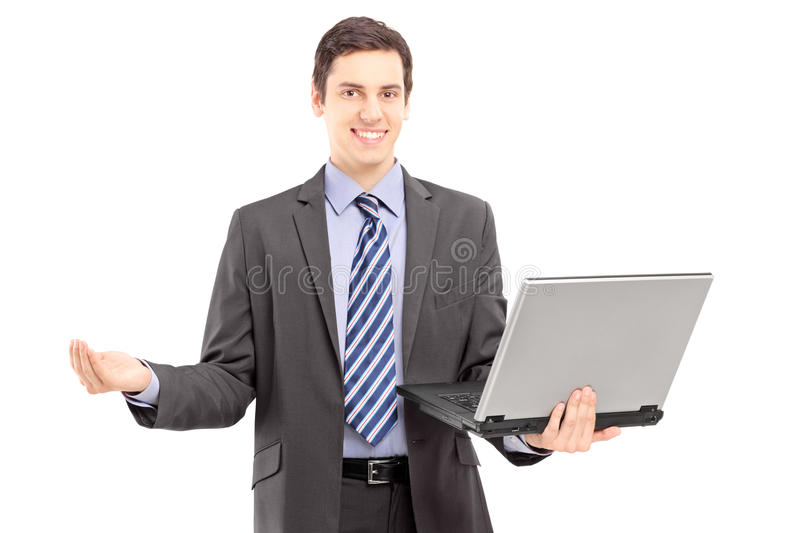 Download Young Man In A Suit Holding A Laptop And Gesturing With Hand Stock Image - Image: 31147263