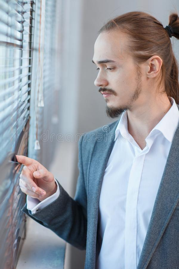 Young man in a suit near a large office window stock photo