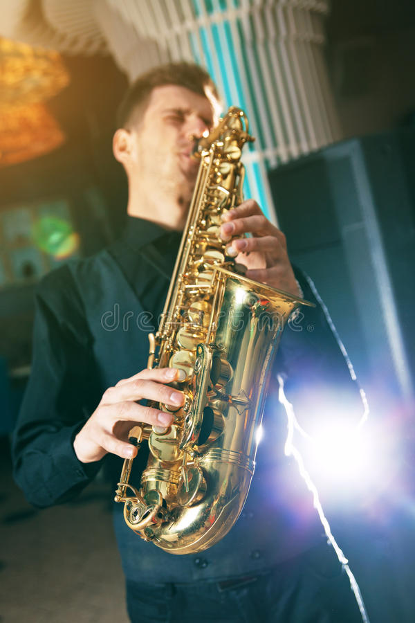 Young man in suit playing on saxophone royalty free stock image
