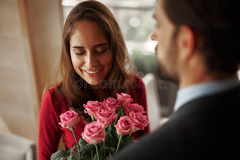 Young man in suit presenting lady bunch of roses. Concept of romantic celebration. Close up portrait of smiling beautiful lady getting bouquet of flowers from stock image