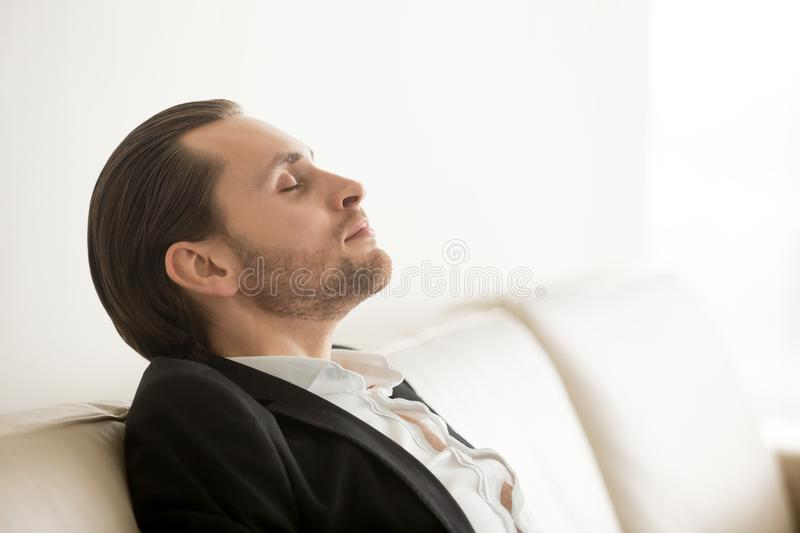Young man in suit resting or meditating with eyes closed. stock photo