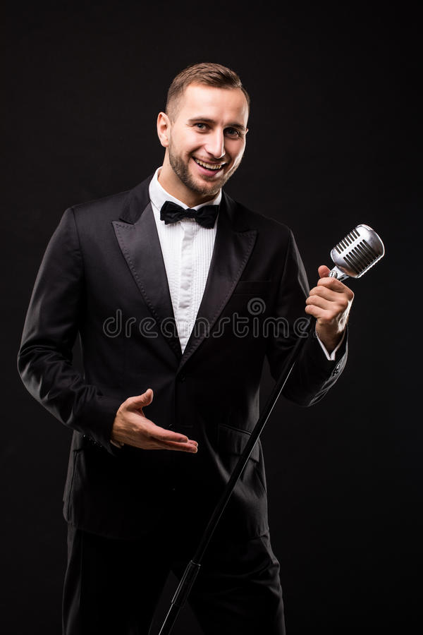 Young man in suit singing over the microphone with energy. Isolated on dark background. Singer concept stock photography