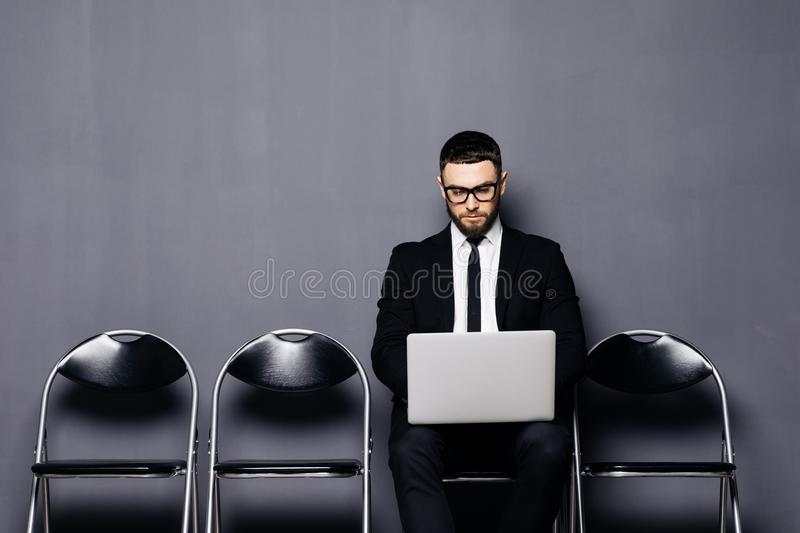 Young man in suit sitting on chair with laptop and waiting for job interview against gray background stock photography