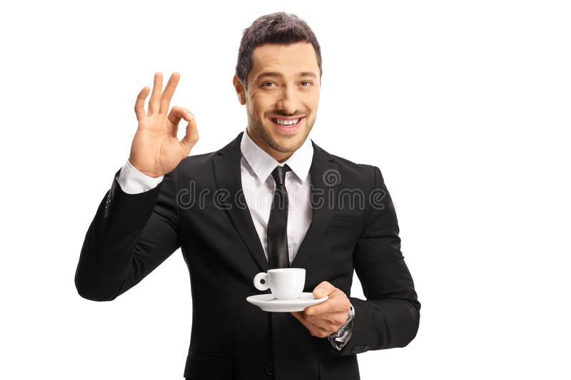 Young man in a suit and tie with a cup of coffee gesturing great with hand stock image