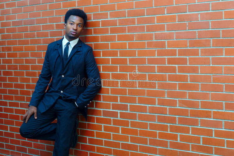 Young man suit and tie orange brick wall modern confident clothing stock images