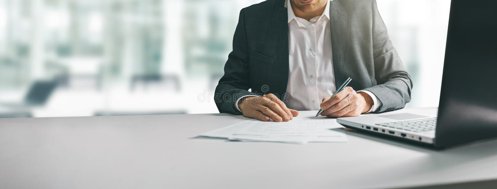 Young man in suit writing business papers at desk in modern coworking office stock photos
