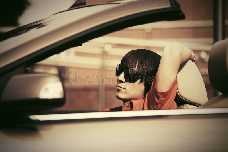 Young man in sunglasses driving convertible car. Young handsome man in sunglasses driving convertible car royalty free stock images