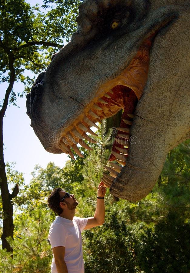 A young man holds the dinosaur behind the tooth. Dinosaur has an open mouth full of sharp teeth. stock photography