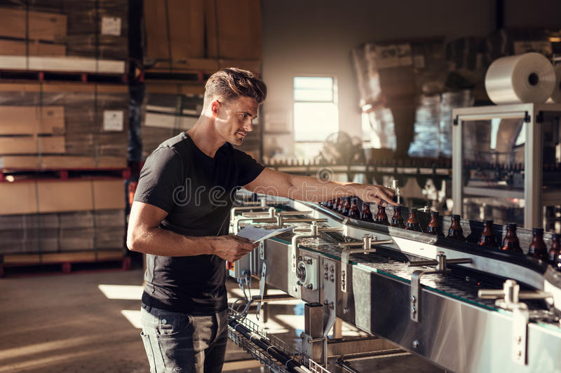 Young man supervising the beer production at brewery. Man working at alcohol manufacturing factory. His is standing near a bottling machine stock images