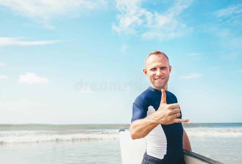 Young man Surfer portrait showing surfer`s famous Shaka sign gesture in camera when he comming with long surf board to waves. royalty free stock photo