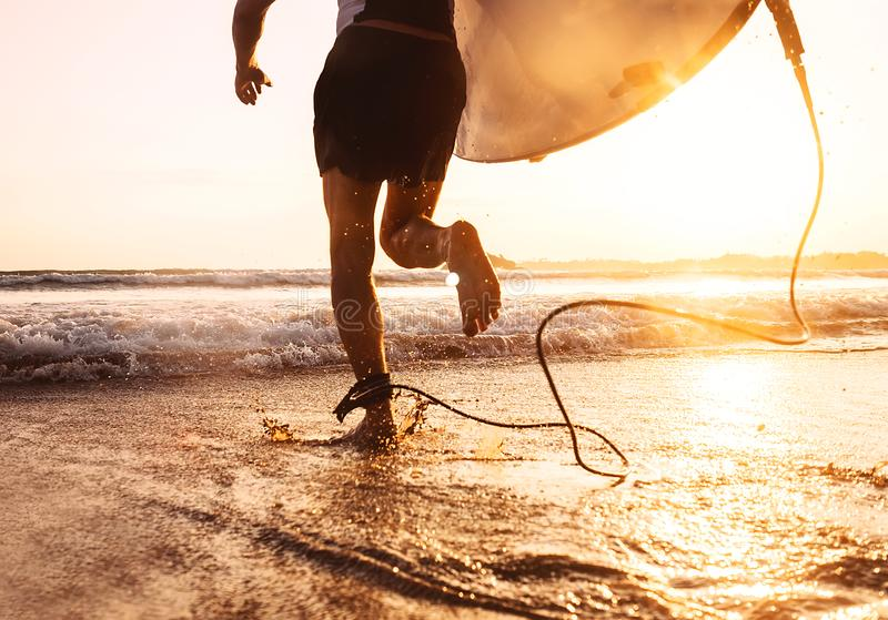 Young man Surfer taking surfboard and running with long surf board to waves on the evening sunset sky background. Active holidays stock photos