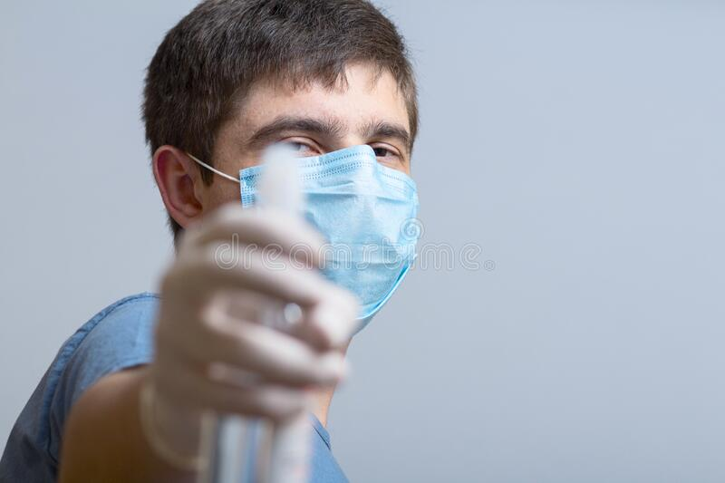 Young man in surgical mask holding up bottle of disinfectant spray on a gray studio background, fight against spread of infection. Quarantine measures, concept stock image
