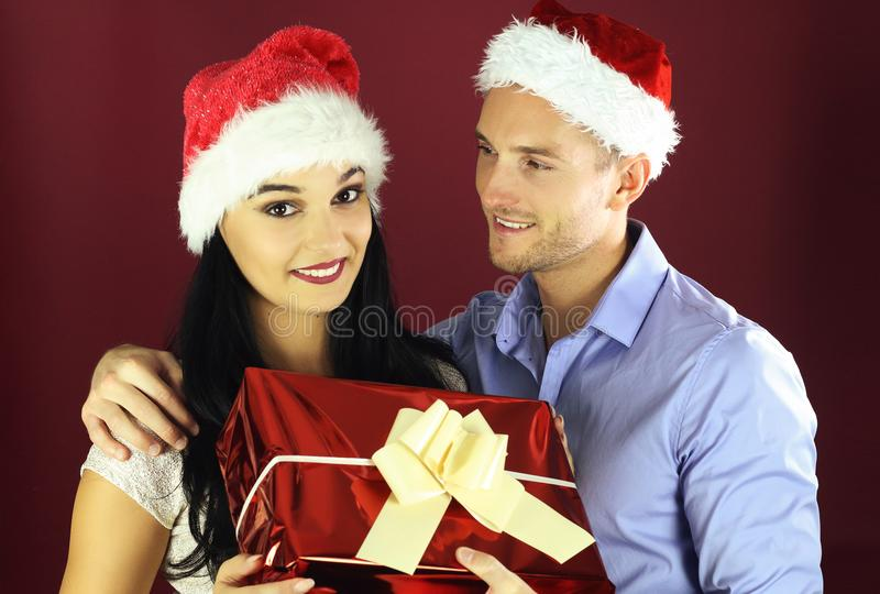Young man surprise his girlfriend with a present for Christmas stock photography