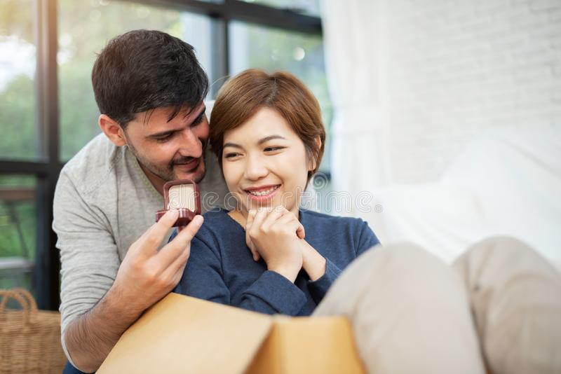 Young man surprising his beautiful girlfriend. royalty free stock photography