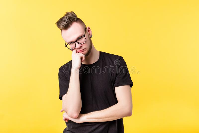 Young man suspicious wary bored look skepticism. Young man looking at camera. Hand on chin. Suspicious wary incredulous bored look emotion. Doubt skepticism stock photo