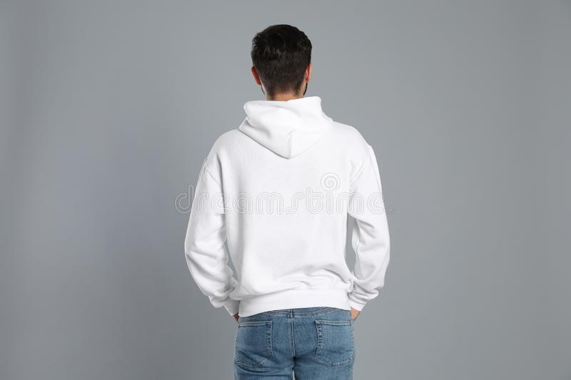 Young man in sweater on grey background stock photos