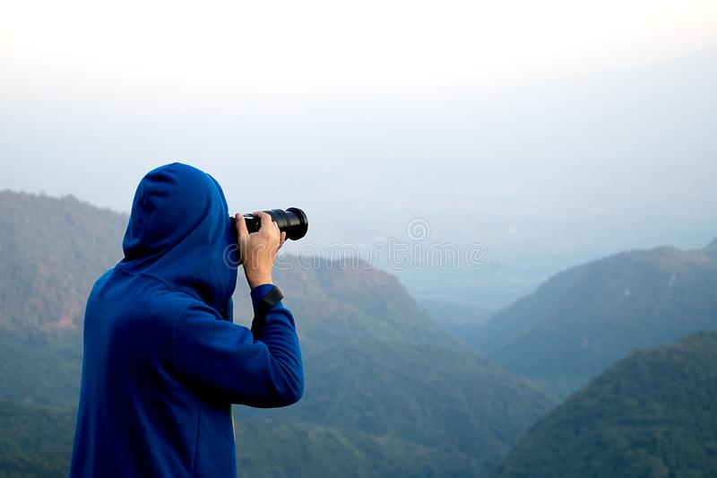 Young man in sweater with hood taking a photo on top of mountain at Doi Ang Khang Chiang Mai Thailand. Young man in blue sweater with hood taking a photo on top royalty free stock photo