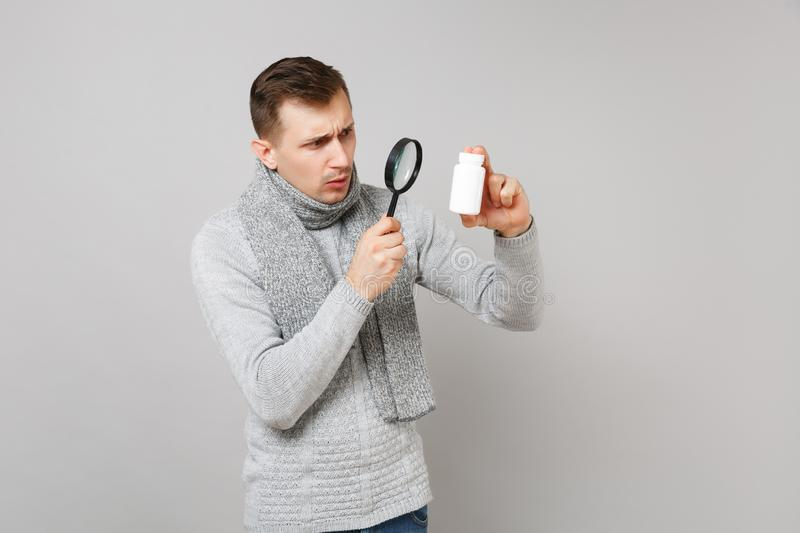Young man in sweater, scarf holding, looking on medication tablets, aspirin pills in bottle behing magnifying glass royalty free stock photography