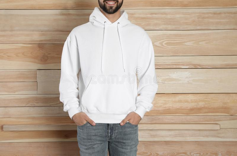 Young man in sweater at wooden wall. Mock up for design royalty free stock images