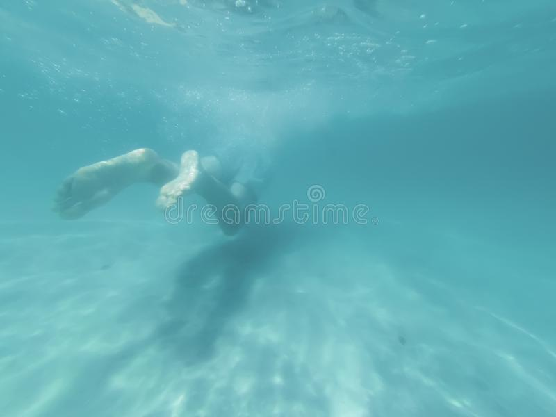 Young man is swimming in the blue deep sea. Underwater shoot royalty free stock images