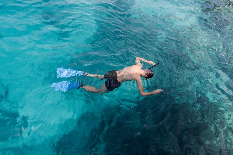 Young man swimming and snorkeling with mask and fins in clear blue water. Male snorkeling in the sea. clear blue water stock image