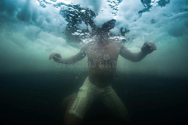 Young man swims in the ice hole royalty free stock photos