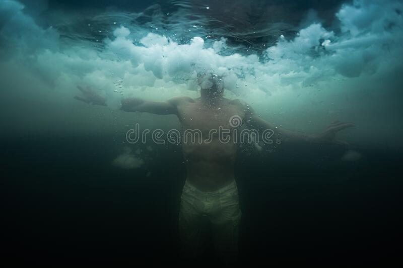 Young man swims in the ice hole stock image