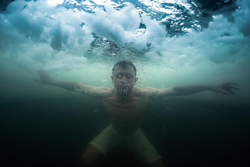 Young man swims in the ice hole stock photos