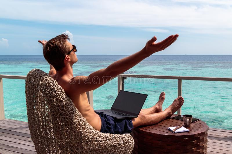 Young man in swimsuit working on a laptop in a tropical destination. arms raised, freedom concept. Digital nomad concept. working in the maldives. Clear royalty free stock photo