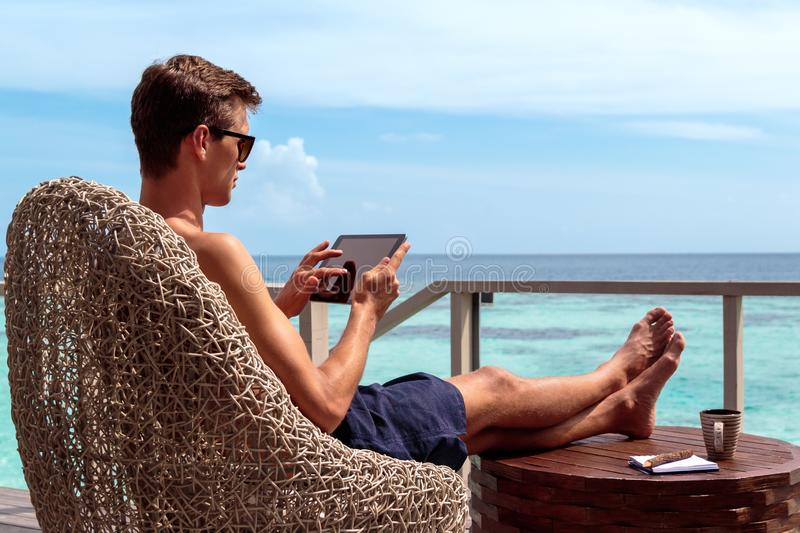 Young man in swimsuit working on a tablet in a tropical destination. Digital nomad concept. working in the maldives. Clear turquoise water as background stock photography