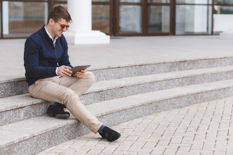 Young man with tablet computer sitting on stairs stock photo