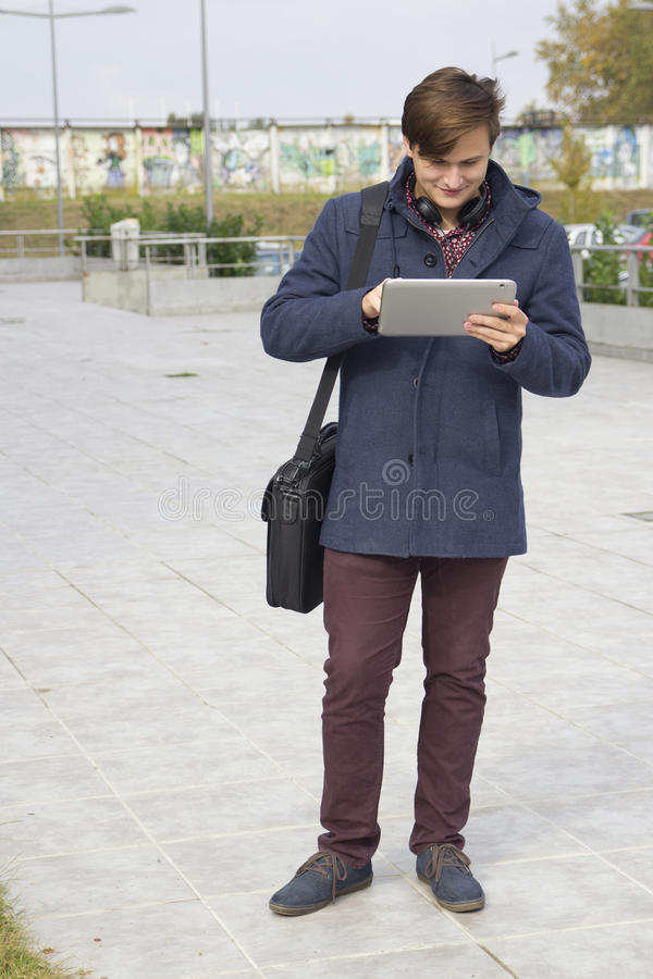 Young man with a tablet. Selective focus and small depth of field, lens flare royalty free stock images