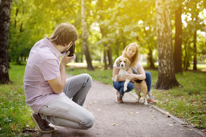 Young man take a shot beautiful woman with dog in sunny summer park. Date or walking stock image