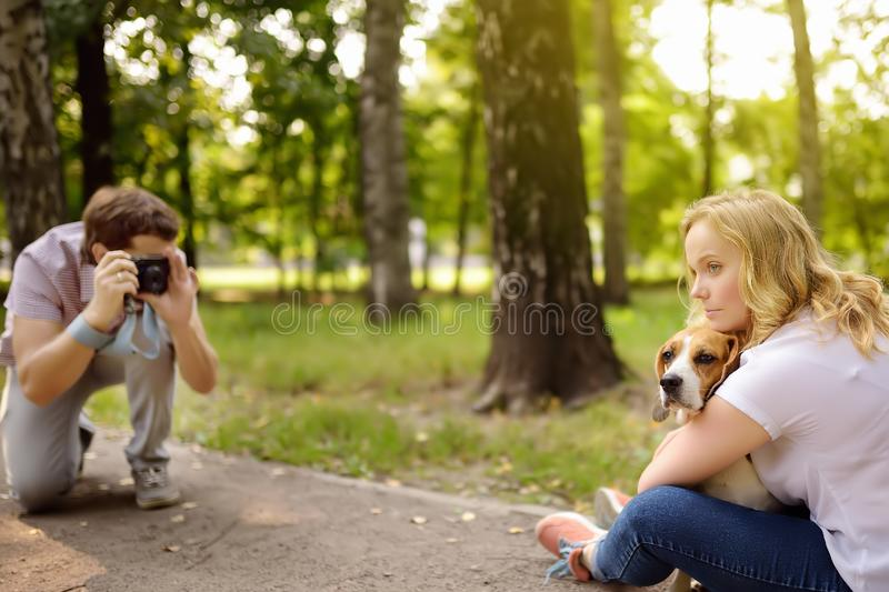 Young man take a shot beautiful woman with dog in sunny summer park. Date or walking royalty free stock image