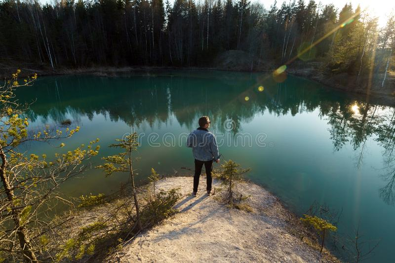 Young man take travel photos - Beautiful turquoise lake in Latvia - Meditirenian style colors in Baltic states - stock photo