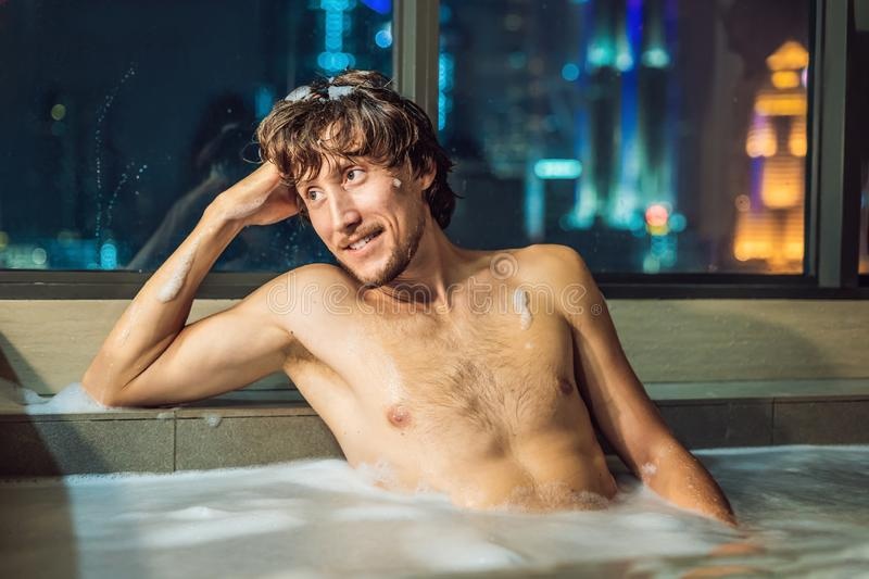 A young man takes a bath against a panoramic window with a view of the night city stock photography