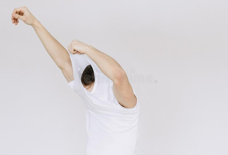 A young man takes off his T-shirt. Isolated gray background stock photography