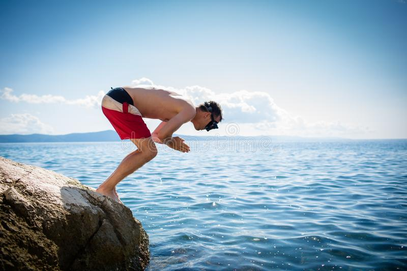Young man  taking a dive in the sea stock photography