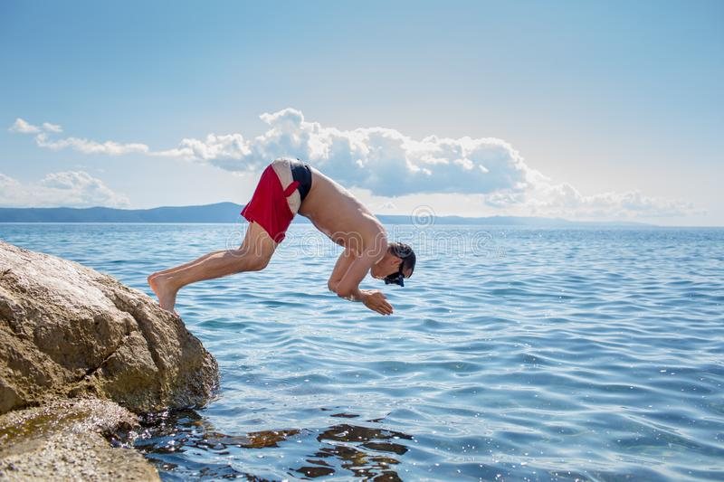 Young man  taking a dive in the sea stock photos