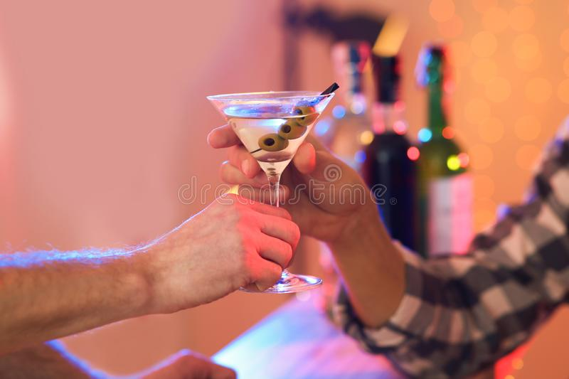 Young man taking martini cocktail from barman in pub royalty free stock image