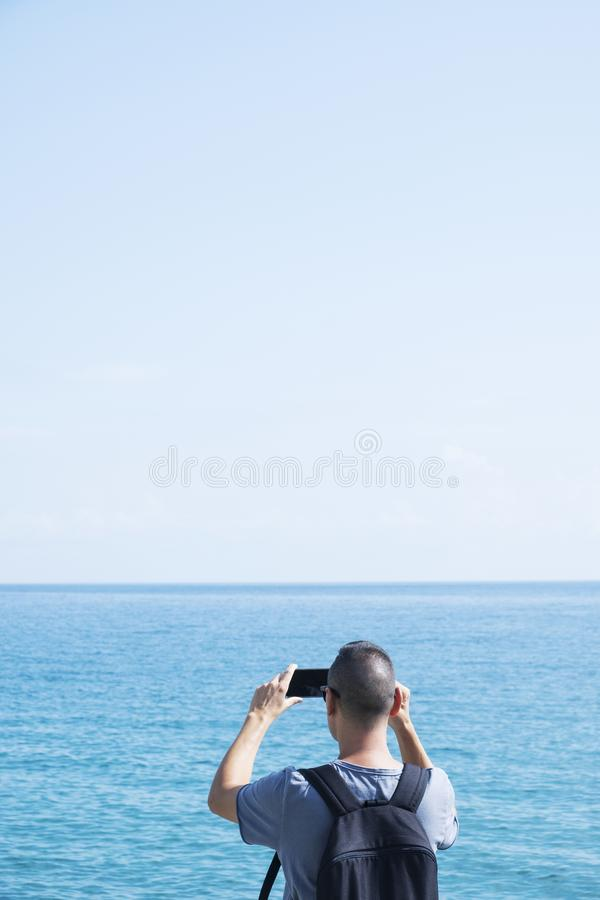 Young man taking a photo of the sea. A young caucasian man, wearing a blue T-shirt and carrying a backpack, seen from behind, taking a picture of the sea with stock photos