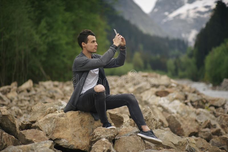 Young man taking a photo with his mobile phone stock photos