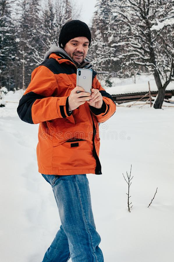 Man taking picture, smiling on winter snow day stock image